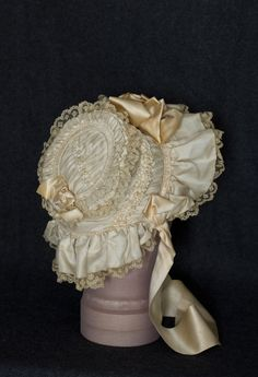 "1850s bonnet Fancy cream colored silk bonnet with elaborate trim and soft ruffled brim, ruched and pleated to create a highly textured design. The crown, back, and inside of the brim are embellished with satin ribbon roses; lined with matching organdy and is outlined with organdy ruffles. The back-neck curtain and brim are ruffled and trimmed with lace. The ties are of wide satin ribbon. The bonnet is 7"" from front to back."