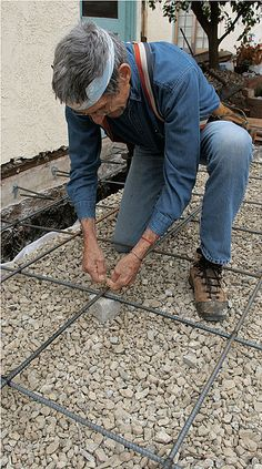 A rebar grid works better than steel mesh to prevent cracks. Held together with tie wire, a rebar grid set on 2-in.-tall concrete spacers stays put during the pour and the screeding. Wire mesh often ends up at the bottom of the slab, where it can't provide structural support.