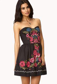 A strapless A-line dress featuring a floral print. Sweetheart neckline. Shirred waist. Zipper pla...