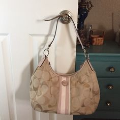 Coach handbag Gently used coach handbag. Tan with pink trim. One interior zipper pocket and 2 open pockets. Pink leather shoulder strap. No holds. No trades. 20% off bundles. Coach Bags Shoulder Bags