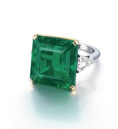 A SUPERB EMERALD AND DIAMOND RING  Set with a rectangular-shaped emerald weighing approximately 24.59 carats, flanked by triangular-shaped diamonds, mounted in platinum and 18k yellow gold