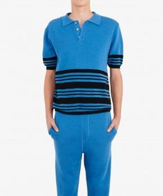Classic sports polo made of high quality merino wool knitted at an extra-fine gauge. Intarsia stripe report on the sleeves and bottom. The placement of the stripes skews the usual proportions of the body for added interest. Inspired by the 'dilettante at leisure' this polo forms part of a full tracksuit and offers a new take on casualwear. Featured on the catwalk.