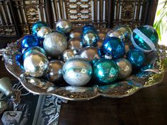 Gorgeous silver bowl full of blue ornaments.