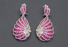 Jolies boucles d'oreilles en or gris 750MM, dessinant des motifs ailés recouverts de rubis et diamants taille baguette et brillant, total des diamants : 2 carats environ, poids : 14,7gr. brut.  Estimation 3.200/3.500€