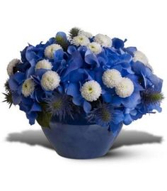 This dreamy blend of fresh blue and white flowers in a blue jardiniere is a sign of a wondrous season!