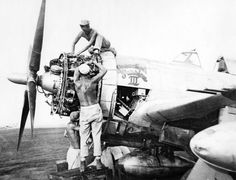 Ed Myslivecek is pictured atop a P-47 Thunderbolt fighter plane while working on its engine on Morat Island, New Guinea in December 1944.