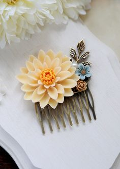 Vintage Inspired Large Ivory Chrysanthemum Flower Statement Hair Comb. Wedding Bridal Hair Comb.  This is a vintage inspired flower collage hair comb made with a large ivory Chrysanthemum resin flower, and smaller flowers in dusky blue and brown colors. I securely set these flowers and a brass leaf on a antique brass filigree comb. This statement hair piece would be a beautiful bridal comb or as a unique gift for someone special.  Size of comb: approx.2.5 x 2.9 (at the widest point) or 65mm…