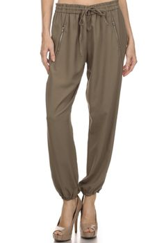 Out Of Africa Pants - These silk like loose fit joggers are this season's new cargo pant this fall. With an elastic waist and zipper trim pockets, they're easy to wear and comfortable. Pair these pants with some stunning gold heels for ladies night or with some flat booties and a tee for some weekend fun. Available in Brown. 100% Polyester.