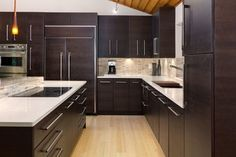 This looks slightly familiar... Bamboo floors, travertine backsplash tiles, amber pendant lights and an onyx waterfall countertop add organic warmth to the contemporary, clean-lined kitchen. For an even more modern touch, the cabinet grain runs horizontally.