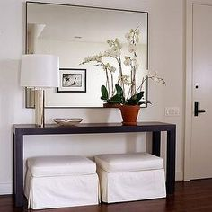 entrances/foyers - skirted ottomans, black console table, Elegant Foyer Slipcovered white ottomans and modern wood console table with chrome