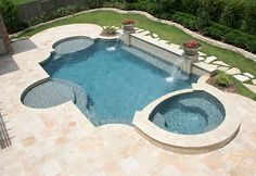 This is a beautiful backyard with classic contemporary styling. The back beam of the swimming pool is raised and accented with two pedestals. The pedestals each have a sheer descent water fall flowing into the swimming pool. On top of the pedestals is a b