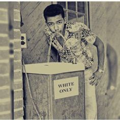 """Stylish black man takes a sip from a """"whites only"""" water fountain 1960s."""