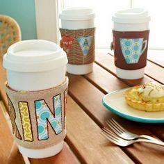 Handmade Travel mug Cozie. Get the size wrap for a standard coffee travel mug. Cut letters or shapes from different patterns of fabric to embellish the cozie. You will get these pretty cozies for you own or your friends as gifts. See how to do it
