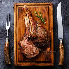 телячьи рёбра - Roasted beef ribs on bone on wooden cutting board with knife and…