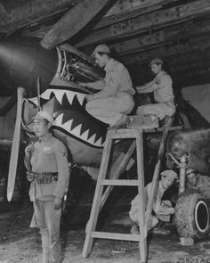 A Curtiss P-40 being serviced by unit mechanics while a Chinese soldier stands guard.