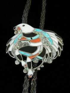 Hand Crafted Old Pawn Indian Jewelry Zuni Inlay Bolo Tie  by John Lucio (d)  John was born in 1919 and began making jewelry in 1950. His specialty was this detailed eagle dancer design that he crafted into bolos, bracelets, buckles and more. He prided himself on his detail and workmanship and his work is highly sought by collectors. This piece was inlaid with turquoise, coral, abalone, mother of pearl and jet. This piece is unmarked, suggesting it is one of his earlier pieces.