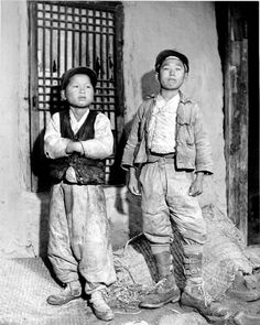 Two boys stand before their home in Chunju. Korean War, 1950-53. G. Dimitri Boria and U.S. Army, Center for Korean Studies Digital Archive, USC.