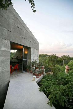 This sculptural structure, built entirely from poured-in-place concrete, houses the studio of a creative couple who are avid gardeners. The workspace is tuck...