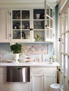 Another kitchen I love! Love how beautifully displayed everything is, the white cabinets, the crystal knobs, the marble counters & the marble carving above the sink! Gasp!
