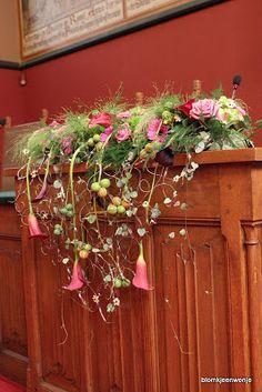 Prachtig bloemstuk op de katheder / spreekstoel. met oa calla, gerbera, roos siergras en komkommervruchten