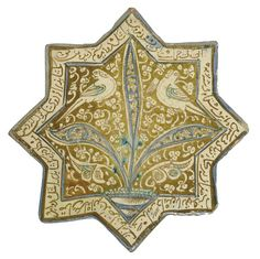A KASHAN LUSTRE, COBALT AND TURQUOISE-BLUE POTTERY STAR TILE CENTRAL IRAN, DATED AH 687/1288-9 AD The decoration with a large central palmette rising from a pond, with two confronted birds on a dense foliage ground, a naskh inscription around the edge 8¼in. (20.8cm.) across