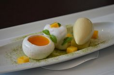 gently poached vanilla bean meringue thats has been hallowed out and filled with mango purée, diced mangoes, toasted coriander ice cream, white tea foam, and dusting of matcha powder