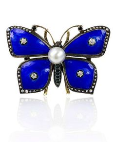 Antique blue enamel and pearl butterfly brooch with seed pearl borders and diamond accents, in silver and 14k gold. Circa 1890.