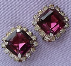 These lovely clip-on earrings probably date from the 1950s. Made from base metal with a silvered finish (finish shows a little wear through age), they are each adorned with shimmering diamante stones surrounding a gorgeous large faceted amethyst glass stone.