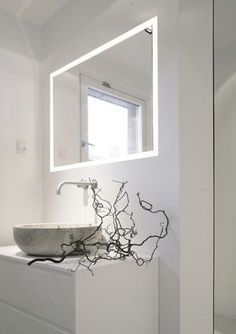 Contemporary white Danish bathroom with illuminated frame mirror over the sink