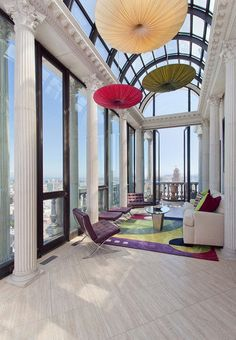 The Hamilton's Penthouse has wood panel floors, a glass barrel-vaulted ceiling, walls of glass, colonnade,  colorful area rug, Barcelona Chairs, hanging artwork and double doors that open to the terrace.