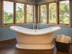 Warm wood tones keep this contemporary bathroom neutral and airy, so as not to compete with the spectacular views enjoyed from the elevated freestanding bathtub. A tub pedestal is a unique modern touch and allows the bathtub to become the focal point of the space.