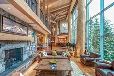 Living area with a glass wall and cedar-log posts and beams in this ski retreat located in Whistler, British Columbia. [1200 × 800]