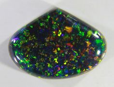 Slocum stone, a black Opal simulant created by adding small pieces of coloured metal foil into a dark coloured silica host.
