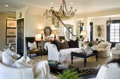 Joy Tribout. I just love this designer's work. In this room and adjoining entry hall she has used the just right amount of black and dark brown to make this basically white space so interesting and gorgeous. Love the chandelier too. Lots of different textures, not too many patterns.