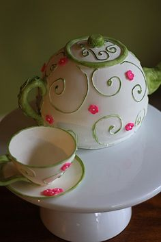 White teapot and cup with green trim and pink flowers