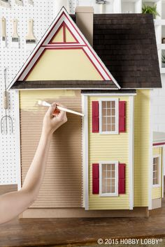 Tips for painting a dollhouse: 1) Start painting at the top, and work your way down. 2) Tape off areas you need to protect, such as the porch floor when you're painting the walls. 3) Use two to three coats for nice, even coverage. 4) Sand the surface and all edges before applying the second and third coats—this will give you a smooth, blemish-free finish.