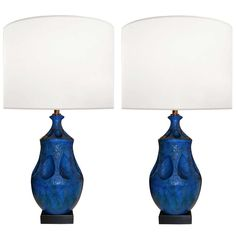 Pair of textured blue ceramic lamps with recessed shapes circling lamps resting on blackened wood bases, Italian C. 1960's