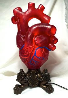 Sculpture of an anatomical human heart, cast in translucent red resin and hand painted.  10.5 tall  Glow from within by 3 alternating LED lights-