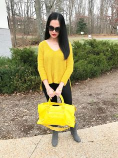 woman wearing yellow Express crossback sweater, black faux leather leggings, gray boots, a pair of Tiffany & Co. sunglasses, and a yellow Balenciaga Giant City purse - outfit idea, fall and winter fashion