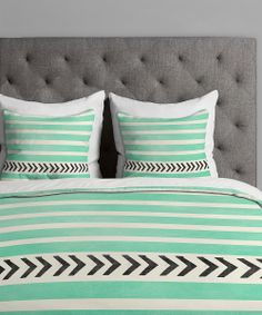 Admittedly love the minty turquoise and chevrons but to be honest, it's the tufted heathered grey headboard that steals my heart in this image.