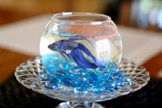 Where this came from is at the link. I think I would love to have a centerpiece for each table with this. Flowers behind it and the fishbowl sit on a book. I would even be willing to buy fish food for each bowl, that way the whole thing would be wedding favors.