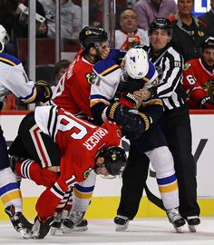 Patrik Berglund #21 of the St. Louis Blues knocks Marcus Kruger #16 of the Chicago Blackhawks to ice as he is held by Ryan Hartman #38 and a referee during a preseason game at the United Center on October 1, 2016 in Chicago, Illinois. The Blackhawks defeated the Blues 4-0.