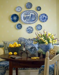Wonderful arrangement of plates on a butter yellow wall. The lemon yellow accents work so well with the blue & white ~ what a cheerful breakfast room.