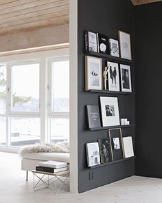 black painted wall with gallery shelves for artwork