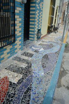 Diseñan banquetas al estilo Gaudí – La iniciativa de Heriberto García Martínez de poner trozos de mosaicos en la banqueta de su casa contagió a sus vecinos de la calle en que vive y, coordinados por él y la artista Lucero Montes, pusieron manos a la obra y ya son varias viviendas de la calle Allende que lucen diseños y pinturas de artistas regios hechos con la técnica trencadis, en una parte del Barrio Antiguo anteriormente conocida como Barrio El Nejayote.