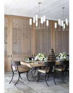 """""""Sliding panels separate the kitchen and dining room; the lacy fretwork is reminiscent of Indian jalis. Klismos chairs—Michael Taylor's Garden chairs—surround a custom Parnassus dining table in white oak from Therien & Co. Ziyi chandeliers from Aero Studios."""" Interior design by Thomas Hamel. Photography by William Abranowicz. """"A Florida Home Goes Globetrotting"""" by Christine Pittel. House Beautiful (December 2010)."""
