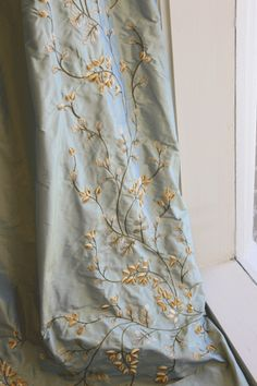Pale blue embroidered silk taffeta drapes maybe master with simple white bedspread?
