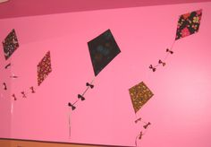 DIY Wall Kites: cover thick cardboard with fabric, add a ribbon to each and hand-sew bows to the ribbon. Attach the kites to the wall with 3M Command strips, and use thick sewing pins to hold the ribbons onto the wall.