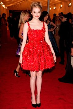 In a sea of floor-length gowns Emma Stone kept things young and fresh by choosing a short red floral applique custom-made number by Lanvin instead. Classic black courts, Lanvin hair pins and a fun up do completed her look. (2012 Met Ball)