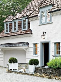 White painted brick exteriori of European manse with blue trim and lantern over front door.